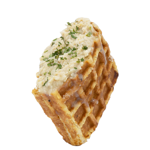 Shredded chicken and thick gravy stuffed waffle sprinkled with Dried Oregano on a white background.